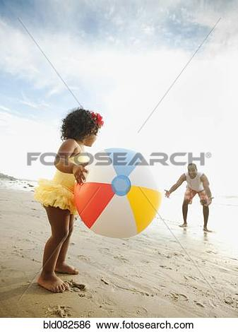 Stock Images of Black father throwing ball on beach with daughter.