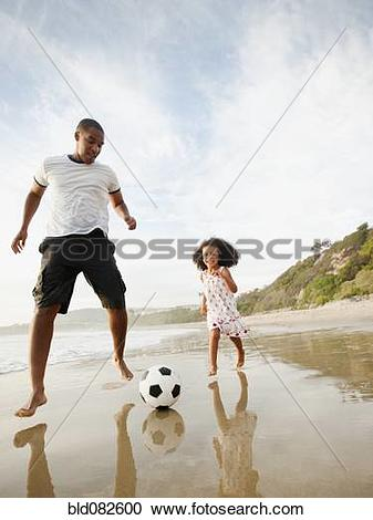 Stock Photography of Black father kicking soccer ball with.