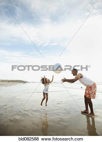 Pictures of Black father throwing ball on beach with daughter.