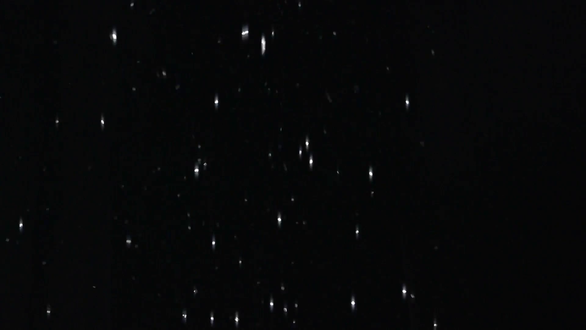 Glitter falling on black background Stock Video Footage.