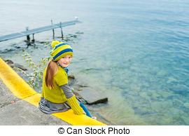 Pictures of Cute little girl sitting on the edge of a swimming.