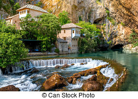 Picture of Woman photographing house on Buna spring in Blagaj.