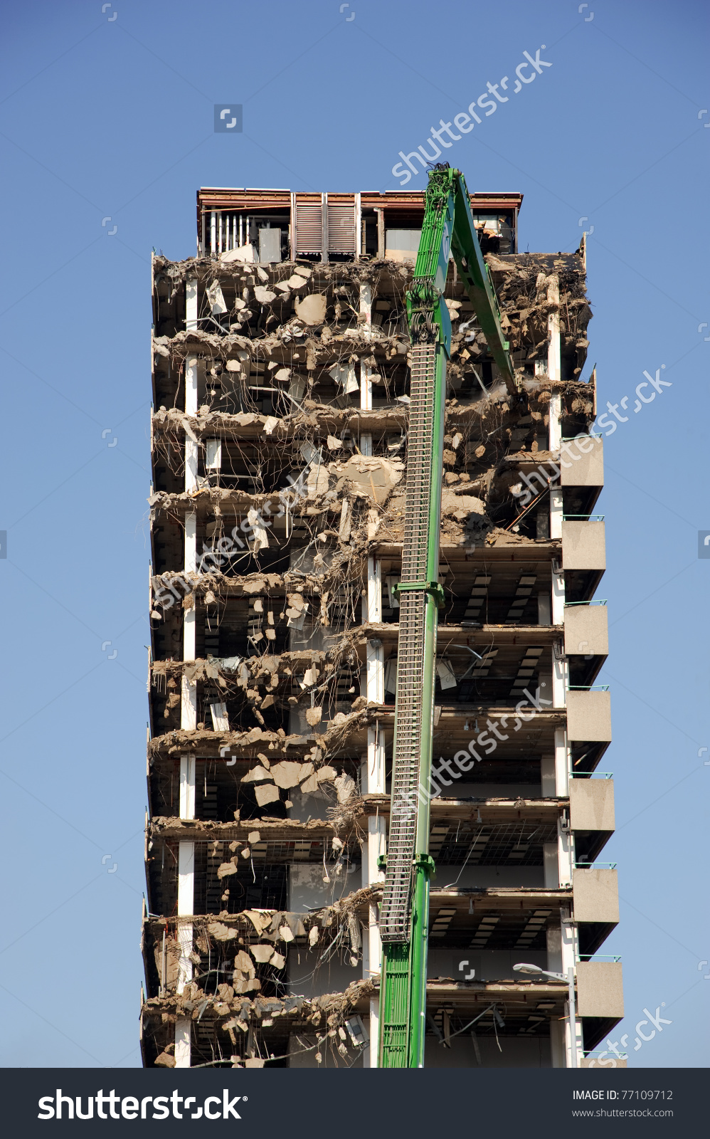 Green Crane Demolishing A Highrise Building Stock Photo 77109712.