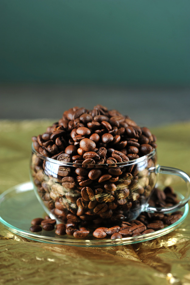 Coffee beans in transparent glass cup on gold Photo.