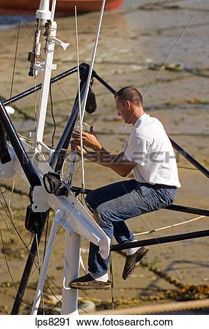 Stock Photography of fisherman fixing radio antenna on trawler.