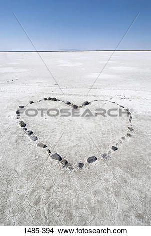Stock Photo of Pebbles arranged in heart shape on a salt flat.