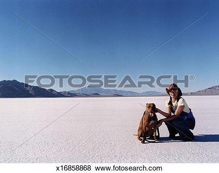 Pictures of Woman kneeling next to dog, Bonneville Salt Flats.