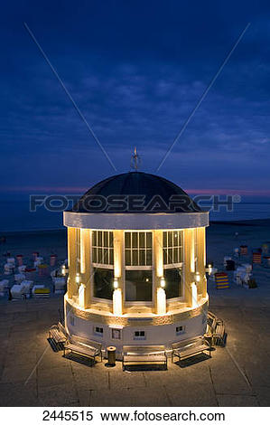 Stock Image of Pavilion and hooded beach chairs on beach at night.