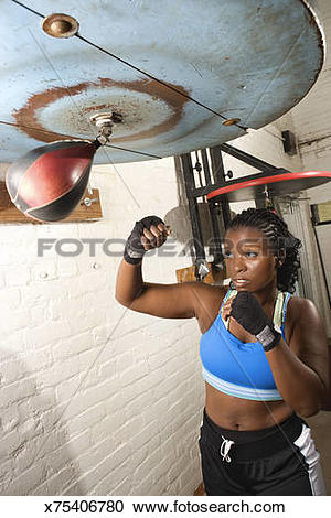 Stock Photography of Woman boxer hitting speed bag x75406780.