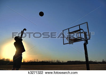 Stock Photo of Silhouette of a Teen Boy shooting a Basketball.