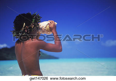 Stock Images of Rear view of a child blowing a conch shell on the.