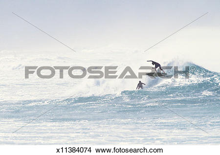 Stock Photo of Two surfers riding breaking wave x11384074.
