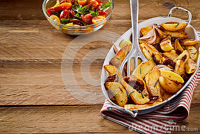 Fried Potatoes With Herbs And Dried Tomatoes Stock Photo.
