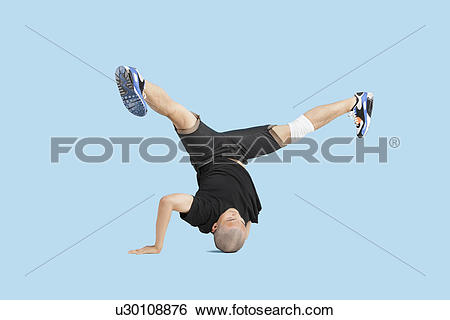 Stock Images of Male dancer doing head stand with legs spread.