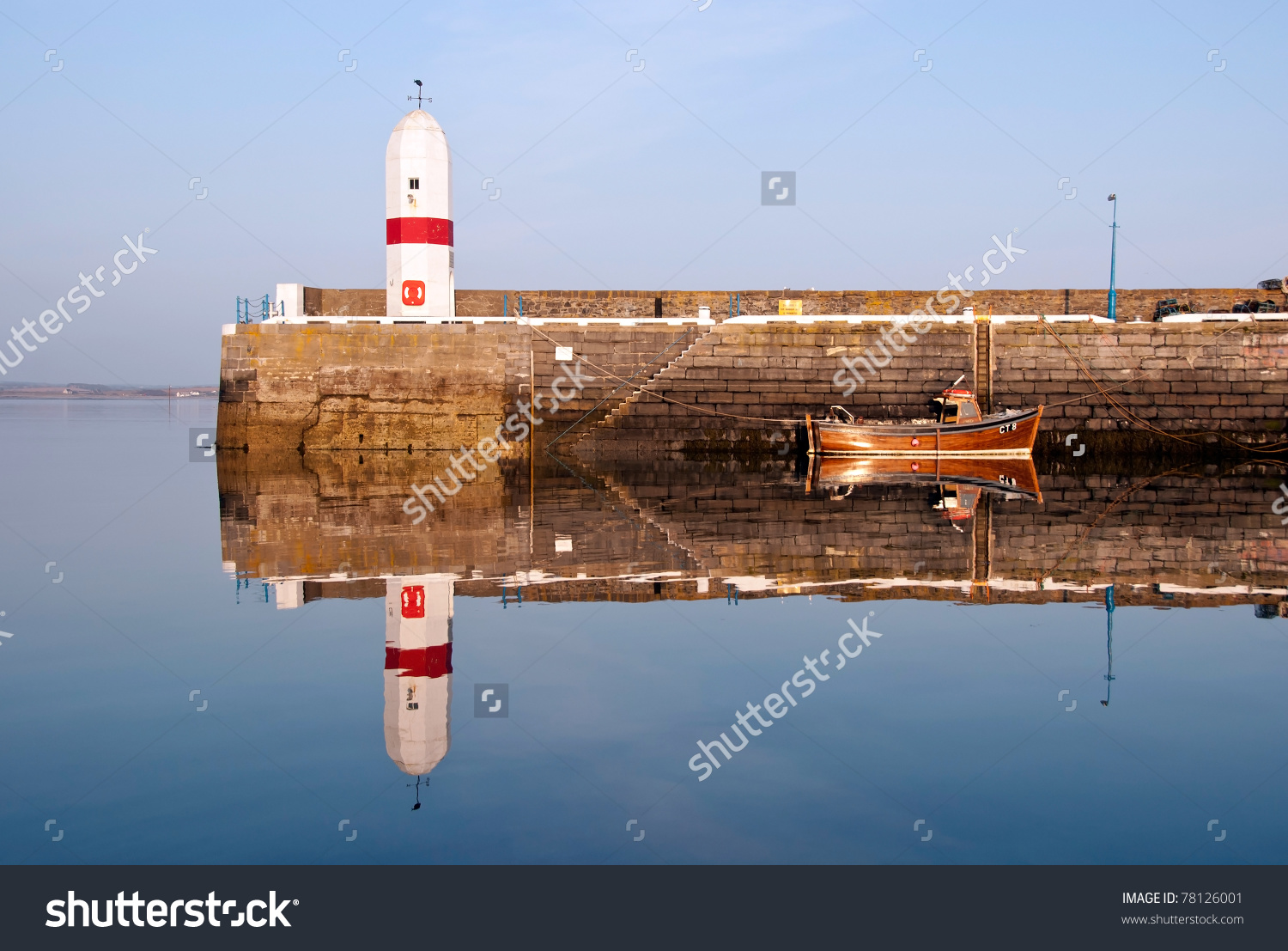 Old Lighthouse On Breakwater Wall In A Harbour With Boat. Sea And.