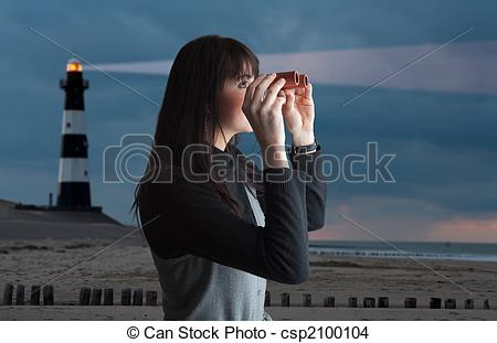 Stock Photo of Girl with binoculars and lighthouse in twilight.
