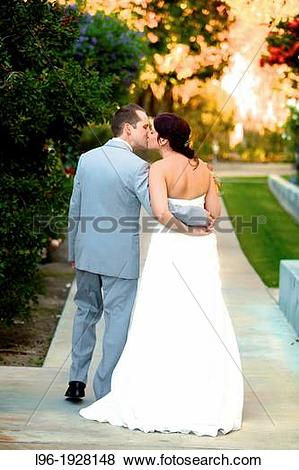 Pictures of bride & groom stealing a moment alone embraced.