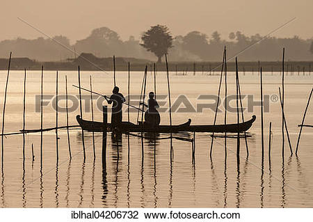 Stock Photo of Two people standing in a dugout canoe, backlight.