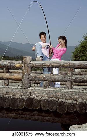 Stock Image of Young lovers fishing together on bridge u13931675.