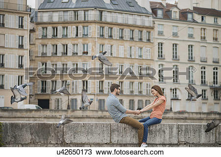 Stock Photo of A couple, man and woman sitting on the parapet of a.