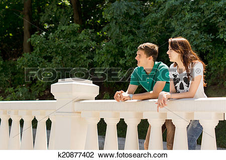 Stock Photo of Young couple leaning on a bridge parapet k20877402.
