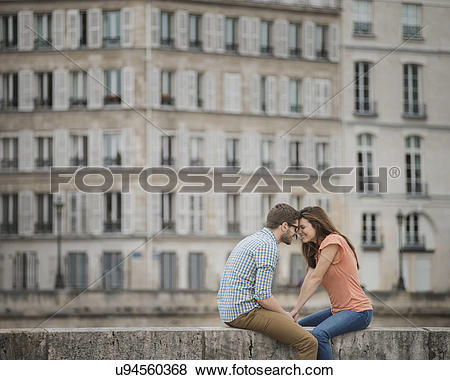 Pictures of A couple, man and woman sitting on the parapet of a.