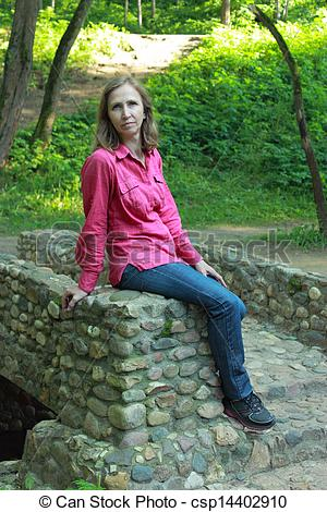 Stock Photography of A woman sitting on a stone bridge parapet.