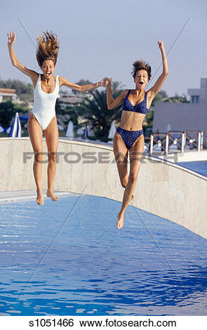 Stock Images of Two young women jumping off bridge into pool.