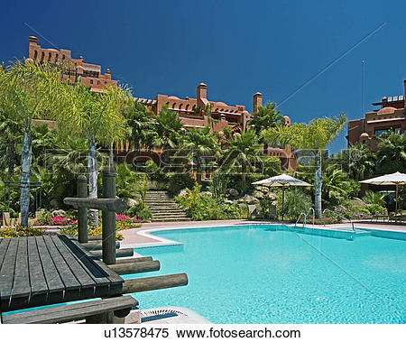 Stock Image of Wooden bridge beside turquoise swimmingpool in.
