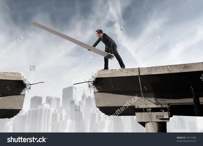 Businessman Rebuilding Broken Bridge Stock Photo 72417469.