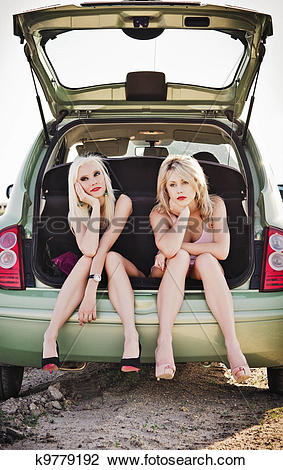 Stock Photo of Two beautiful blonde girls sitting in trunk of.