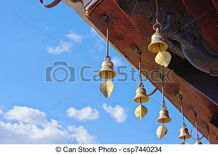 Stock Photo of Bronze bells ringing in the wind under the roof of.