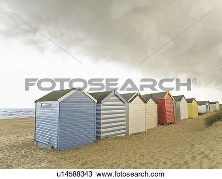 Stock Photo of Beach huts under brooding sky u14588343.