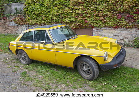 Stock Photograph of England, Somerset, Taunton. A yellow MGB, an.