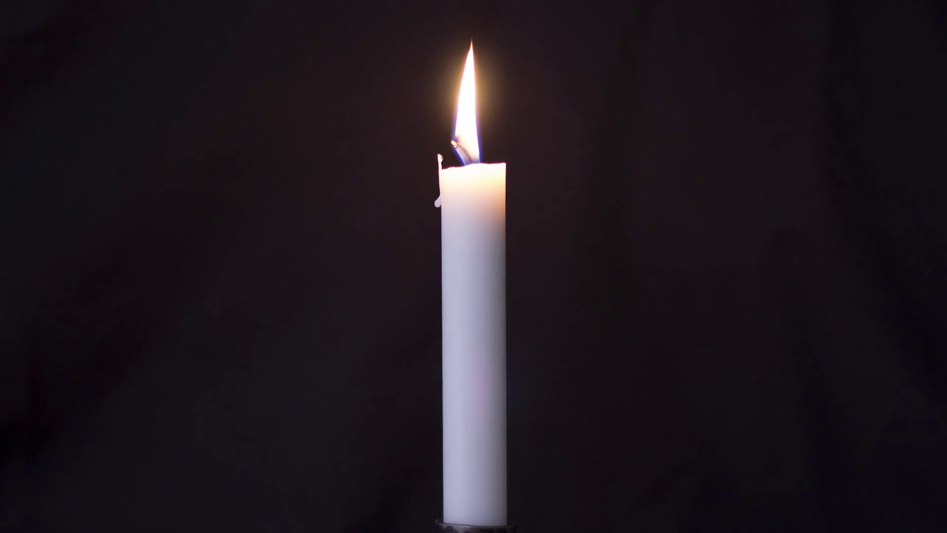 Timelapse of long isolated candle burning with dark background. Eventually  burns out.