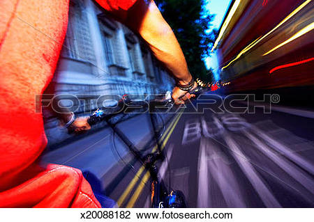 Stock Photo of England, London, young man cycling in bus lane.