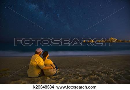 Stock Photo of Romantic Couple On Beach At Night in Cabo San Lucas.