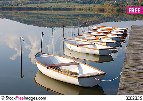 White Boats On Calm Water Surface..