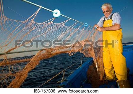 Stock Images of Senior fisherman fishing with nets in his boat.