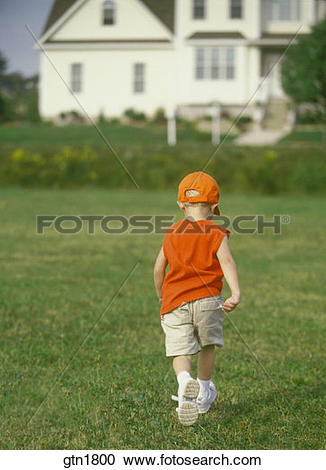 Stock Photography of Small little boy walking away from the camera.