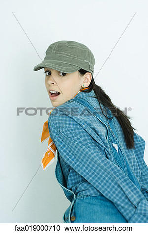 Stock Photography of Teen girl wearing overalls and cap, looking.