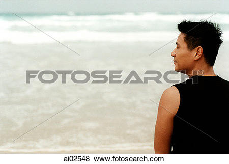 Pictures of Man standing on beach, back to camera, head turned to.