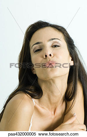 Stock Image of Woman blowing kiss to camera, head and shoulders.