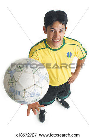 Picture of a young latin male in a yellow jersey tosses up a.