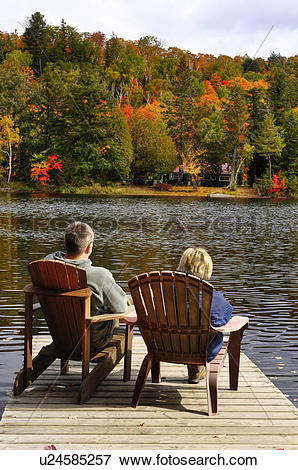 Picture of Couple sitting in chairs on a lake at and enjoying.