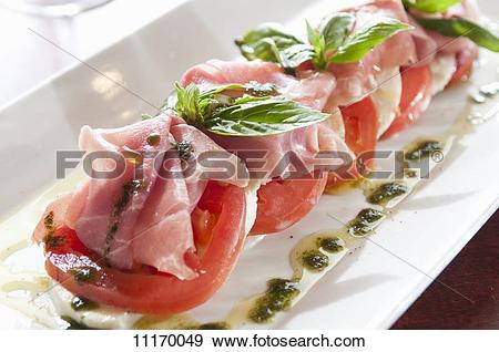Stock Photograph of Caprese Salad with Prosciutto and Herb Sauce.