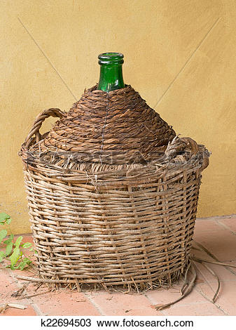 Stock Photo of Antique old demijohn, carboy, by yellow wall.