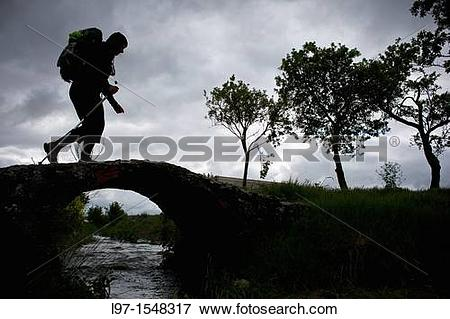 Picture of Silhouette of hiker crossing bridge along the Camino de.