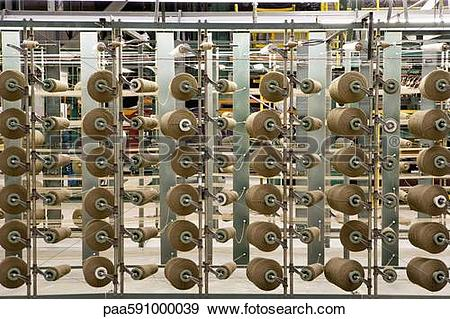 Stock Photograph of Yarn spools on carpet weaving machine.