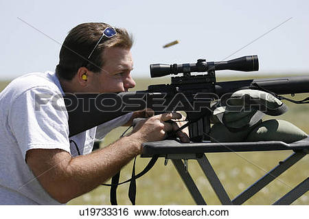 Stock Images of man male shooting rifle ejected cartridge case.